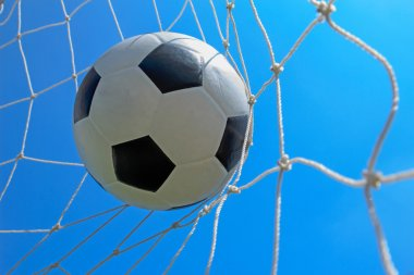 Soccer ball in goal and blue sky