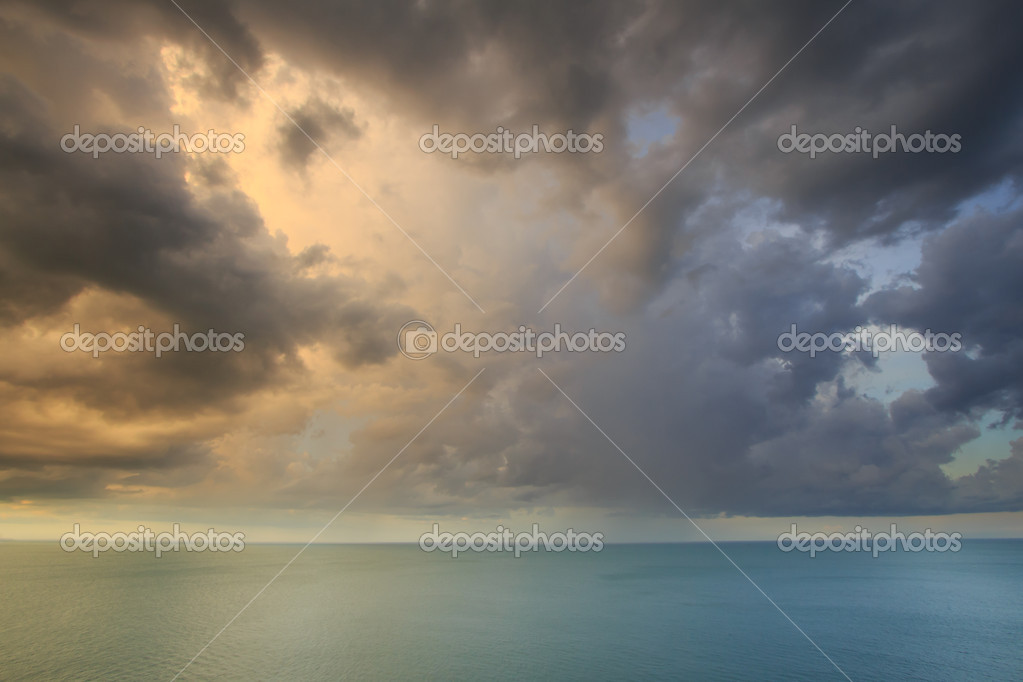 Dramatic tropical rain cloud sky and sea at dusk