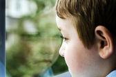 Fotografia triste bambino guardando fuori finestra giorno cupo