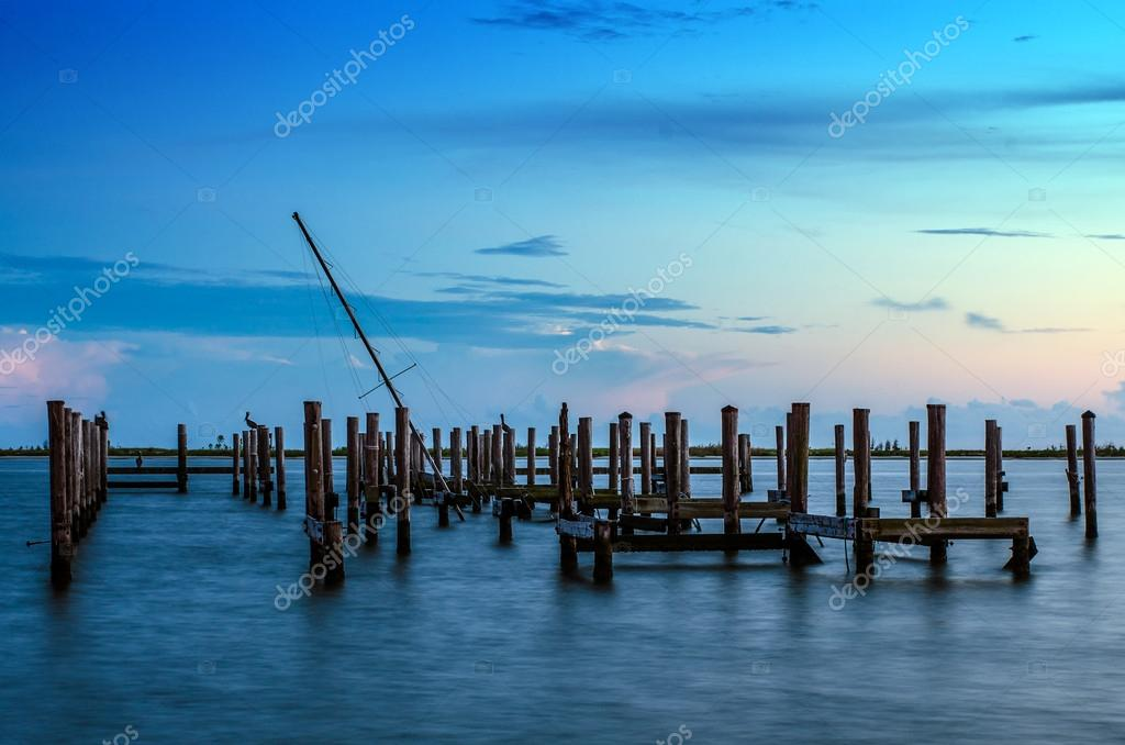 Broken pier and mast of broken ship in water after sunset in Biloxi, Mississippi
