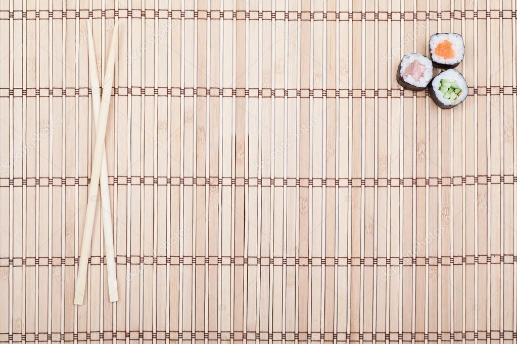 Chopsticks And Sushi Roll On Bamboo Mat Stock Photo