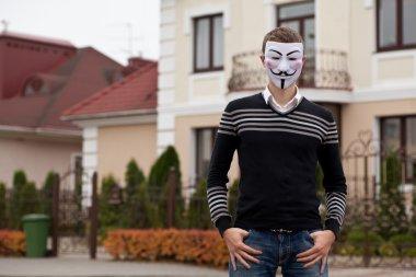 hacker in masked members of Anonymous posing