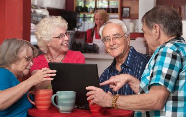 Seniors Having Fun with Computer in Cafe