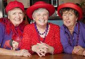 drei ältere Frauen mit roten Hüten