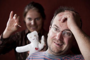 Upset woman with vioodoo doll and guilty man