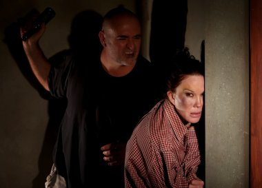 Frightened woman in hallway with menacing man