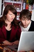 žena a muž zíral s šokem na laptop