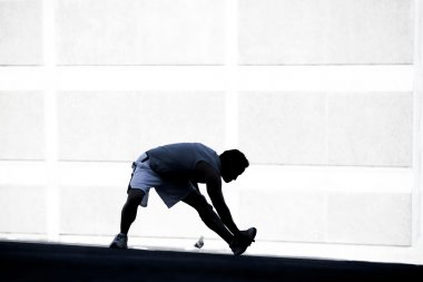 Male runner stretching before a run.