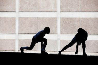 Two women stretching before running.