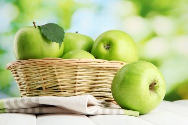 Ripe green apples with leaves in basket, on wooden table, on green backgrou