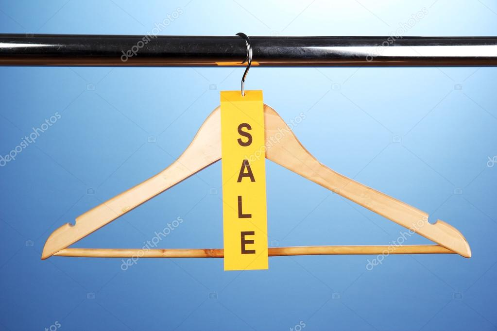 Wooden Clothes Hanger As Sale Symbol On Blue Background Stock