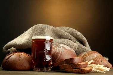 tankard of kvass and rye breads with ears, on wooden table on brown backgro