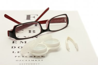 glasses, contact lenses in containers and tweezers, on snellen eye chart ba