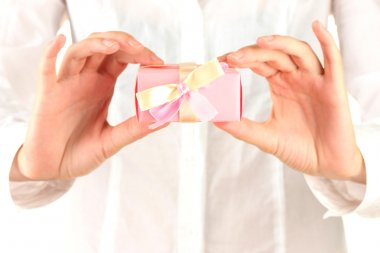 woman holds a box with a gift on white background close-up