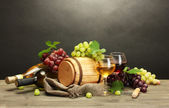 Photo barrel, bottles and glasses of wine and ripe grapes on wooden table on grey