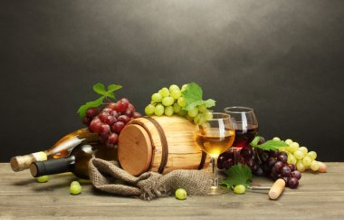 barrel, bottles and glasses of wine and ripe grapes on wooden table on grey