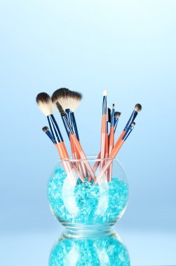 Make-up brushes in a bowl with stones on blue background