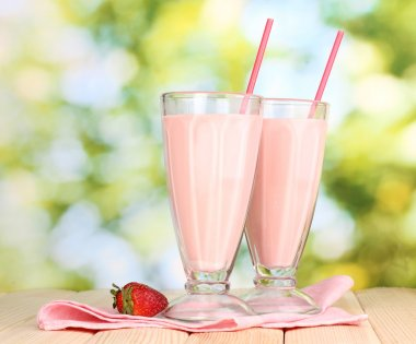 Strawberry milk shakes on wooden table on bright background