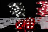 výherní kombinace karet s poker žetony a kostky na černém bac