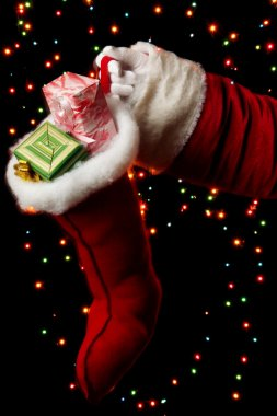Santa Claus hand holding gifts on bright background