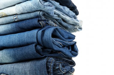 Lot of different blue jeans close-up isolated on white