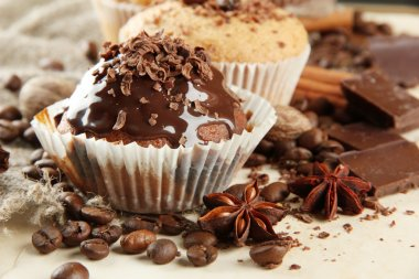 tasty muffin cakes with chocolate, spices and coffee seeds, on beige backgr
