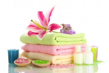 towels with lily, aroma oil, candles, soap and sea salt isolated on white