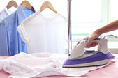 Fotografie Woman hand ironing a shirt, on cloth background