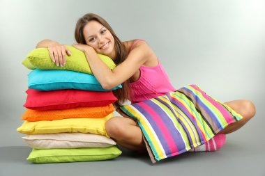 beautiful young girl with pillows on grey background