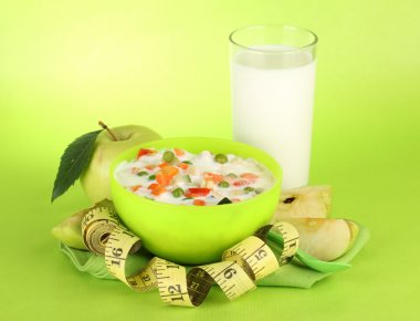 tasty dieting food and glass of milk, on green background