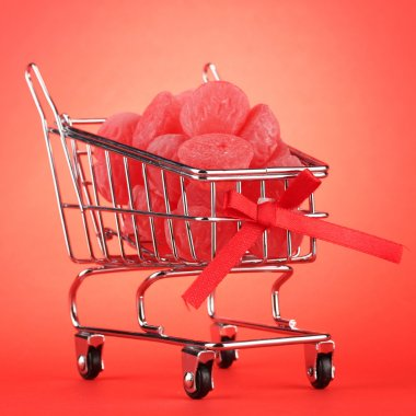 shopping trolley with jelly candies, on red background