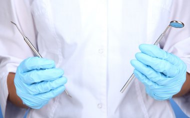 A dentists hands in blue medical gloves with dental tools