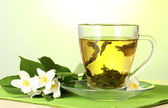 cup of green tea with jasmine flowers on wooden table on green background