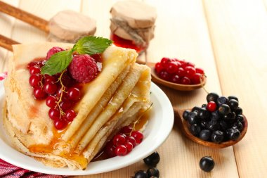 Delicious pancakes with berries, jam and honey on wooden table