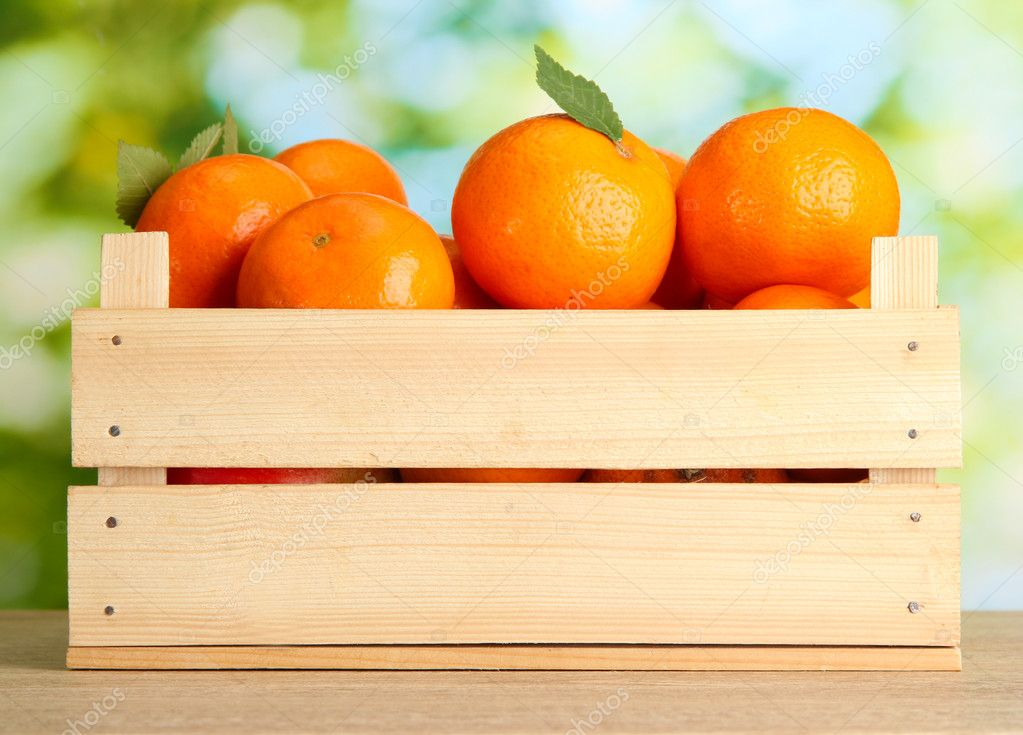 Ripe tasty tangerines with leaves in wooden box on table on green backgroun