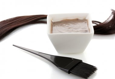 Bowl with hair dye and black brush on white background close-up
