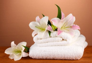 stack of towels with pink lily on a brown background