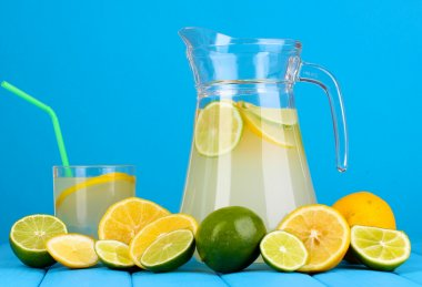 Citrus lemonade in pitcher and glass of citrus around on wooden table on blue background