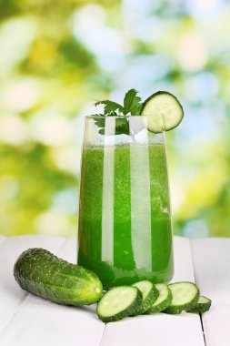 Glass of cucumber juice on wooden table, on green background
