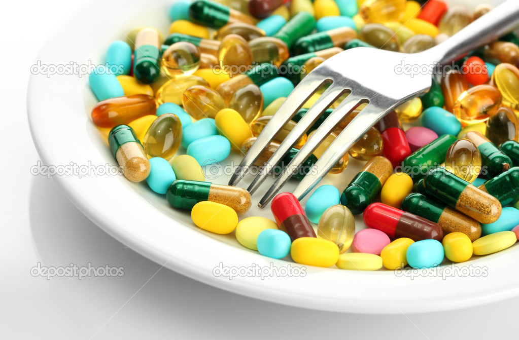 Colorful capsules and pills on plate with fork, isolated on white — Photo  by belchonock