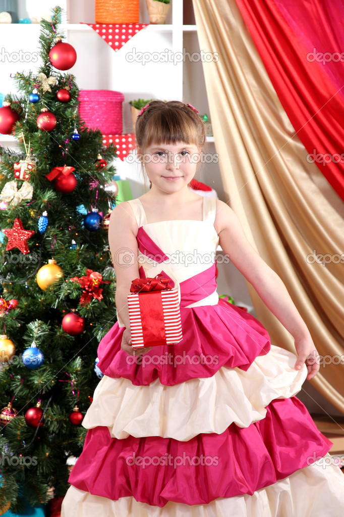31375aca57 Gyönyörű kislány ruha üdülési ajándék a kezükben ünnepélyesen feldíszített  teremben– stock kép