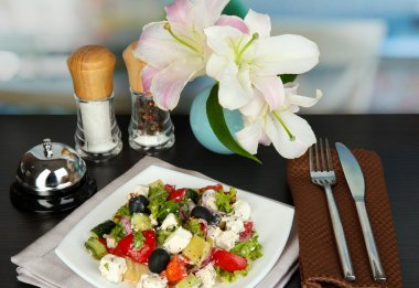 Fresh greek salad on white plate on table on restaurant background