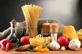 Tészta spagetti, zöldség és fűszerek, a fából készült asztal, a szürke háttér