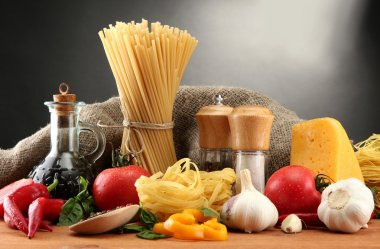 Pasta spaghetti, vegetables and spices, on wooden table, on grey background