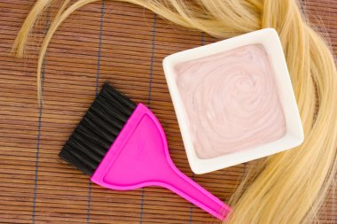 hair dye in bowl and brush for hair coloring on brown bamboo mat, close-up