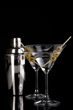 Martini glass with olives and shaker isolated on black