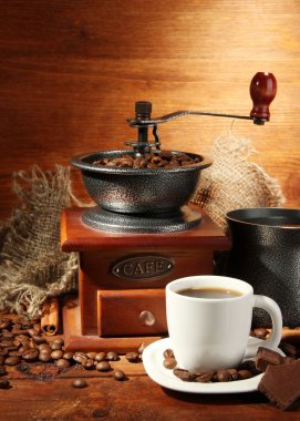 Coffee grinder, turk and cup of coffee on brown wooden background