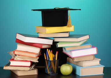 Books and magister cap against school board on wooden table on blue background