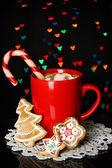 šálek kávy s dovolenou cukroví na vánoční osvětlení pozadí