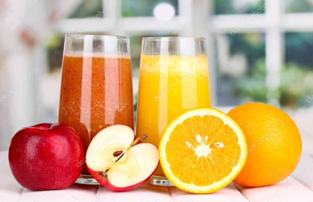 fresh fruit juices on wooden table on window background stock
